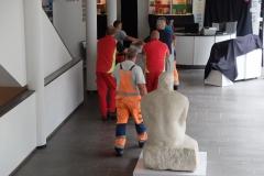 Bauarbeiter transportieren die Einbauten der letzten Ausstellung hinaus